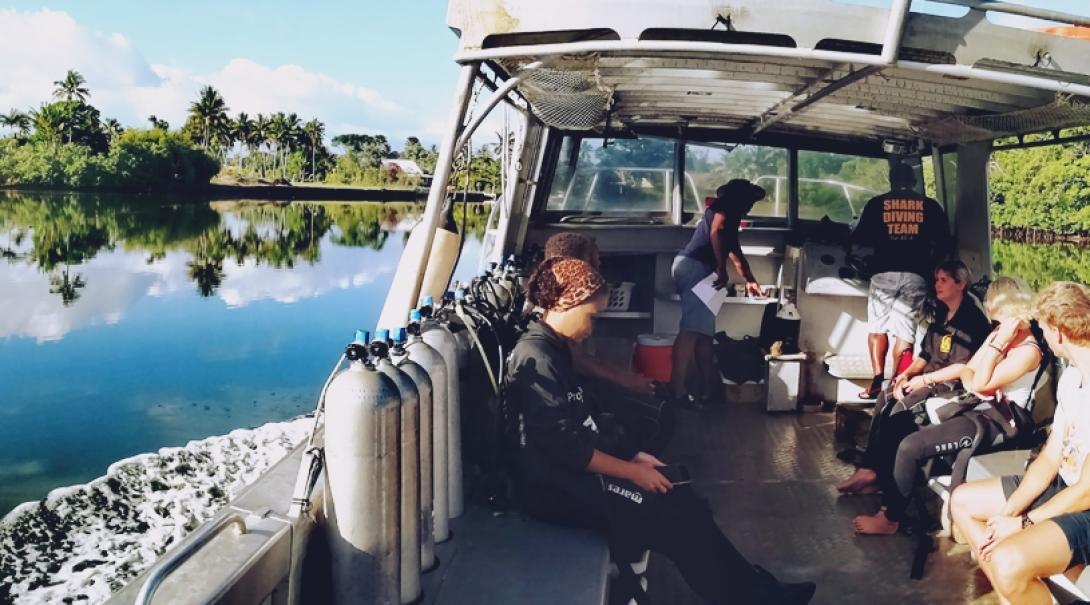 ボートに乗ってフィジーの海でダイビング調査に向かう環境保護ボランティアたち